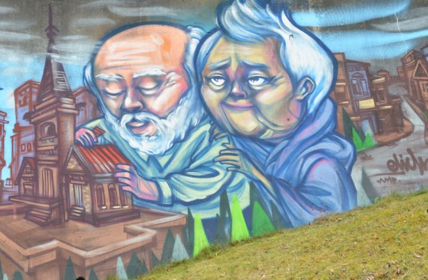 part of a mural by street artist elicser, an older couple. The man has a white beard and is bald.