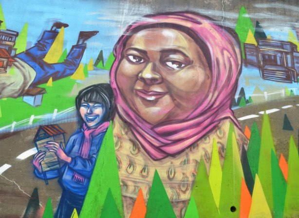 part of a mural by elicser, a woman in a pink head scarf, with a younger woman walking down a road behind her