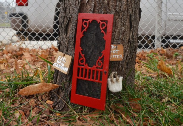 A little red screen door, fairy door, at the base of a tree with two little signs. One sign says Earl Haig gardener and the other says Do not litter.