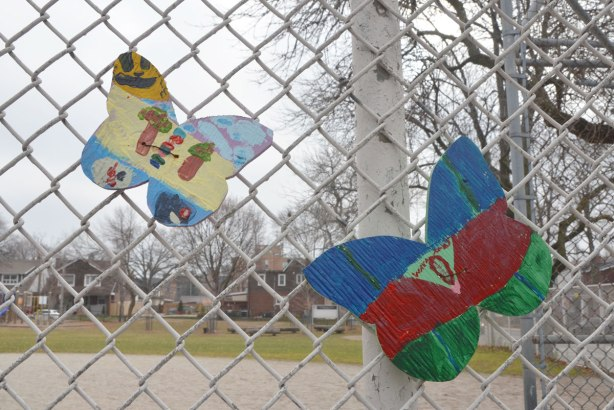 two wood butterfly shapes that have been hand painted by kids and then attached to a chain link fence around a school playground.