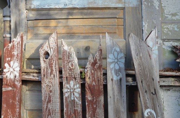 close up of old picket fence that is falling aoart, and a fence made of doors that is behind it.
