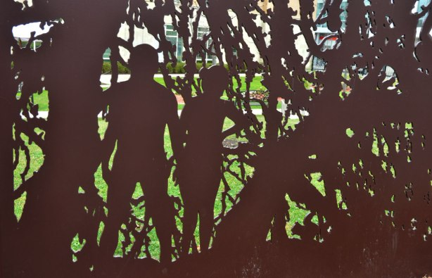 cut outs in a metal wall of people walking through a forest