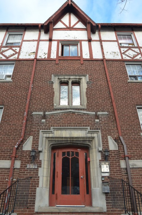 front door and front of building, four storey apartment building in red brick with stone window and door frames.