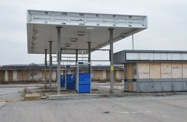 three abandoned fuel pumps at an old unused gas station