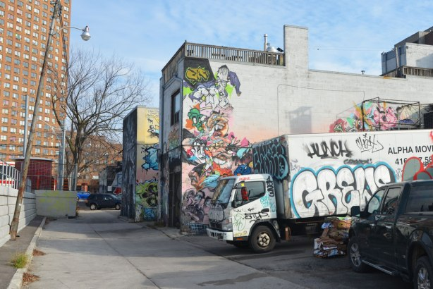 looking down a laneway towards a large brick apartment building. The side of a truck has some graffiti on it - the truck is backed into a parking spot in the lane. The buildings in the lane have graffiti on them.