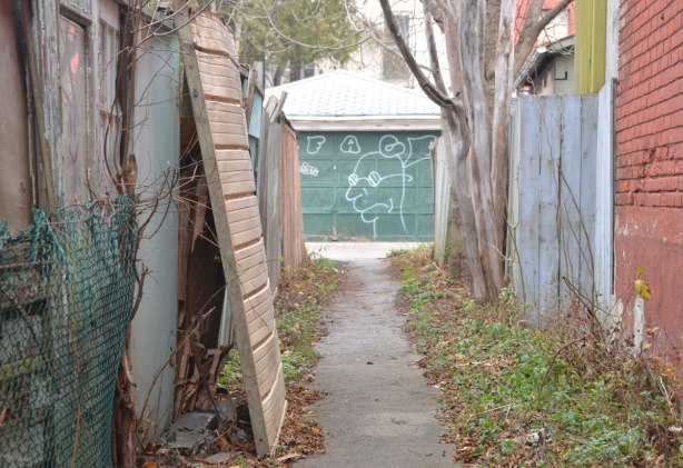 garage door painted green with a white line drawing of an odd shaped face, as seen from looking down a path, fences on either side of the path
