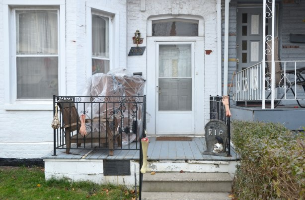 A small porch in front of a house that is still decorated for Halloween, a couple of fake arms and a fake tombstone with RIP on it.