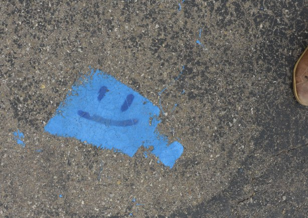 A blue square shaped painted spot on the pavement. Two eyes and a smiling mouth have been drawn on top in darker blue