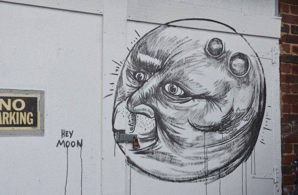 black line drawing on a white garage door in an alley. Round moon shape witha face in the moon.