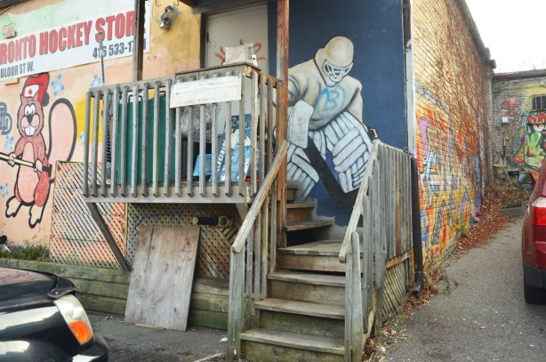painting of a hockey goalie in full pads and helmet painted on a blue door by a small porch in a laneway.