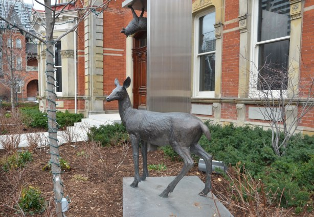 part of an art installation by Eldon Garnet called inversion - A deer in front of a building and a wolf hanging upside down part way up the side of the building
