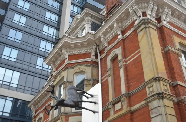part of an art installation by Eldon Garnet called inversion - a large moose seems to be standing against the side of an old mansion that has been renovated and incorporated into a new highrise condo development