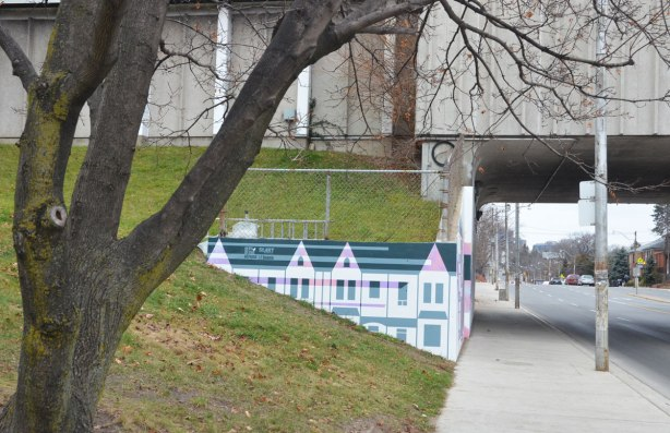 part of a mural by Rob Matejka and Tommy Matejka on the wall on a TTC subway underpass at Keele, a mural of houses on a street, looking north on Keele Street