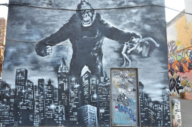 Grey toned mural of King Kong holding a woman over a tall building as he walks through a large city, and towers over it.