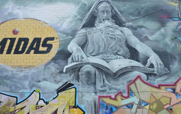 mural of older man in grey tones, with open book on his lap, beside him is the Midas logo (auto repair).