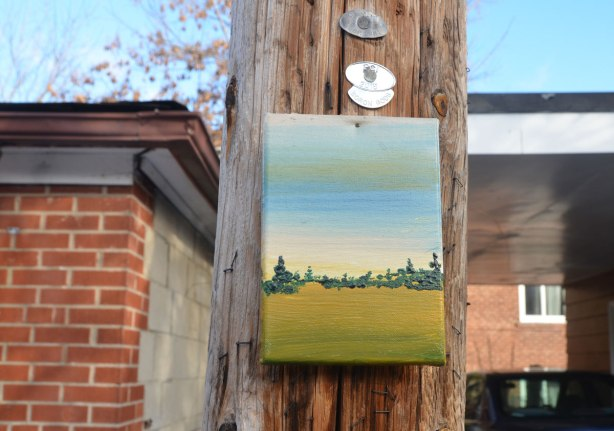 A small landscape painted on canvas and attached to a telephone pole in an alley