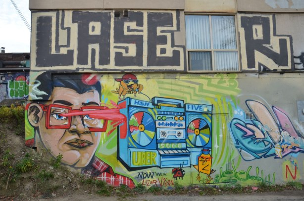 graffiti street art in an alley - a Uber5000 mural of a man with reg glasses and red flashes coming from his eyes. A little birdie is sitting on top of a ghetto blaster