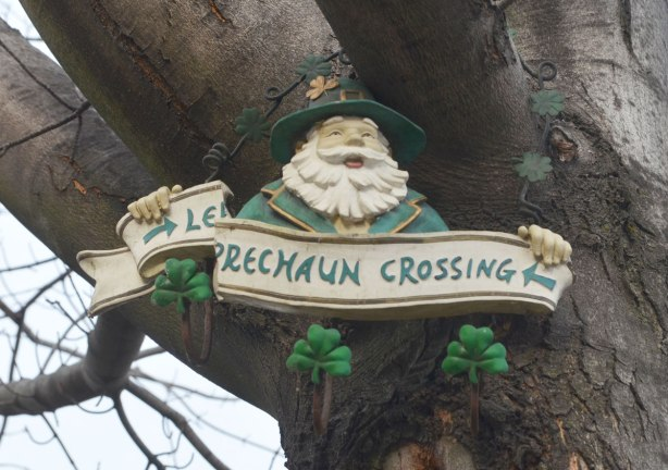 Up in a tree, a decoration with a leprechaun holding a broken sign that says leprechaun crossing.
