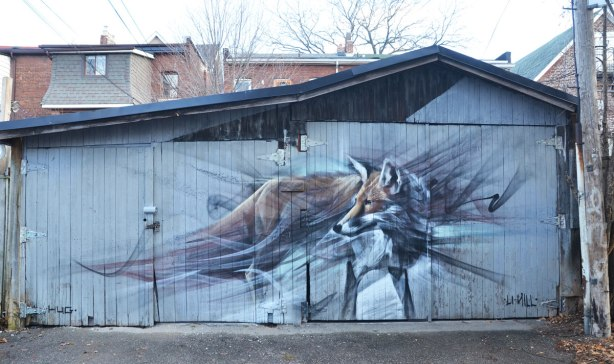 very realistic painting of a wolf (or a dog) on a garage door in a lane.