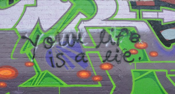 Someone has scrawled Your life is a lie in black over a piece of street art. Someone else has changed lie to life by adding an f