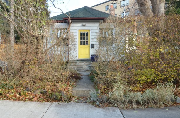 little narrow white bungalow with a yellow front door set back from the road. There is a straight walkway from the sidewalk to the door, and there is a lot of shrubery in the front yard especially near the sidewalk.