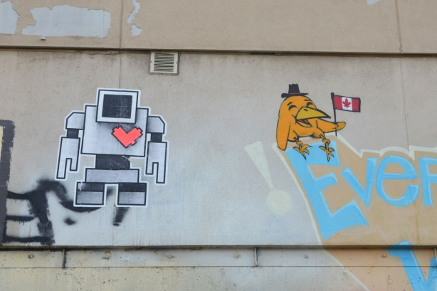 graffiti street art in an alley - a lovebot wheatpaste on a wll beside a Uber5000 yellow bird holding a Canadian flag
