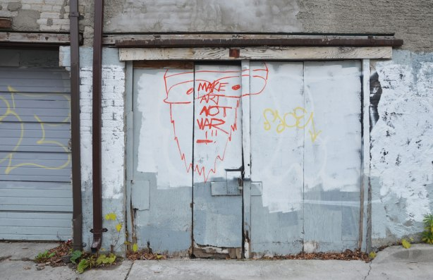 make art not war slogan painted on a garage door in a red line drawing face