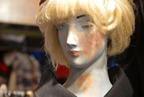 head of an old mannequin with blond wig, one eye is missing, and the covering on her is wearing off.