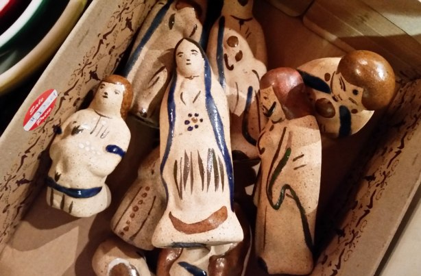 ceramic figures of the Nativity scene, Mary, Joseph, baby Jesus, etc. They are lying in a box that is for sale in a store.