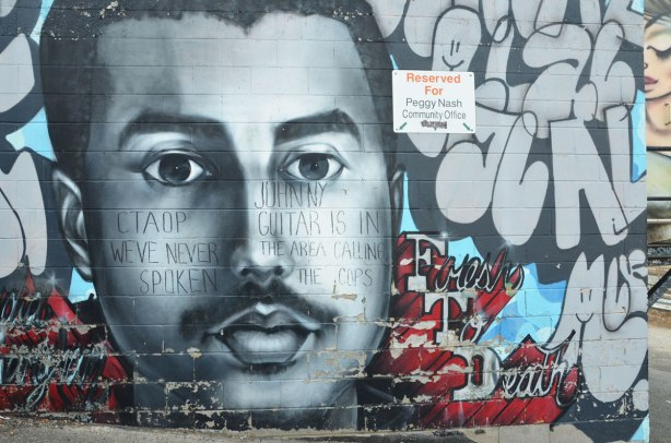 large mural of a young man's face in grey tones. Small moustache, head only,