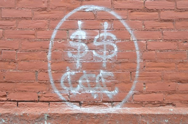 graffiti with two dollar signs and three cent signs on a rust coloured brick wall