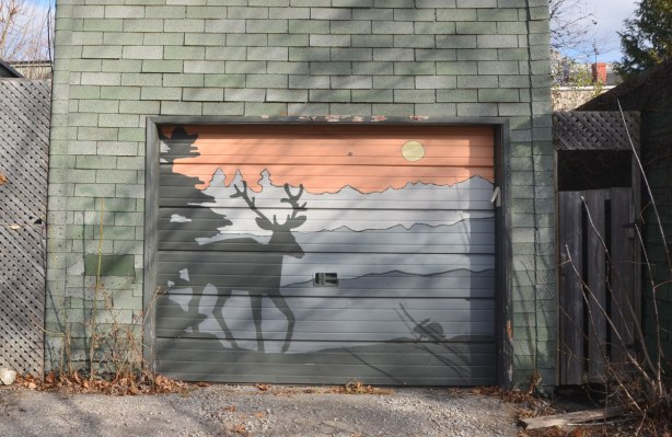 painting on a garage door of a moose at sunset