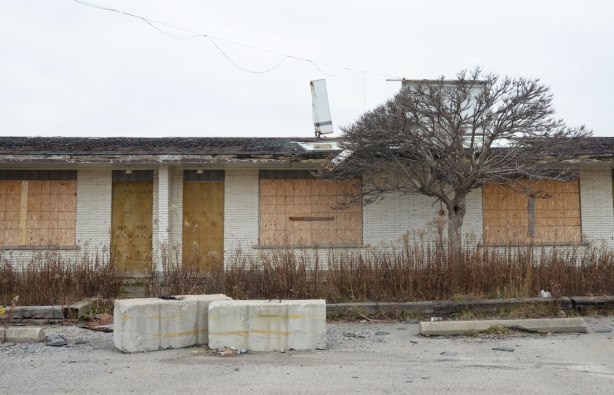 boarded up doors and windows on an old motel, the sign on the roof is broken and part has fallen to the ground.