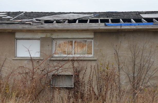 back of motel, some roof shingles missing, inside of windows has been covered, weeds overgrown,