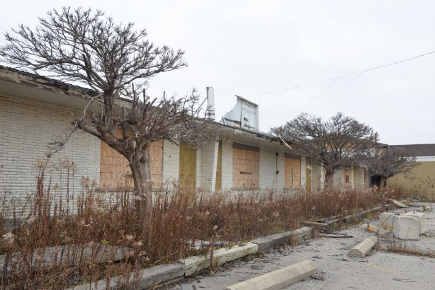 front of abandoned motel Stop 50 on QEW near Hamilton, row of boarded up doors and windows, one storey white brick building
