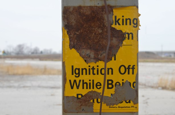 rusted old sign at a gas station that warns you to turn off your ignition while refueling your car