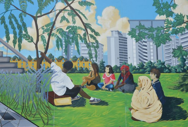 part of a mural celebrating education, a group of people are sitting around in a circle outside while one man is talking