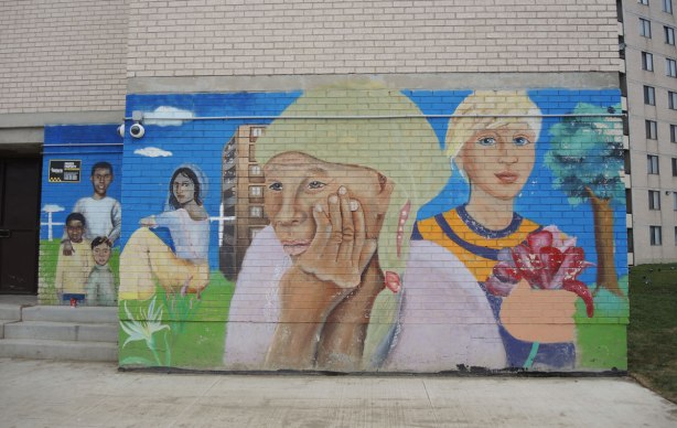 part of a mural on the lower floor of a grey brick apartment building, women, one holding flowers, one resting her head on her hand, one sitting on the grass.