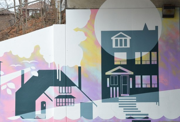 part of a mural showing two houses, with two real houses in the background