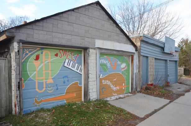 street art on garage doors, musical instruments covering two garages, a guitar, a trombone, also the words sweet sweet music everywhere