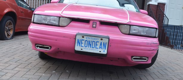 the back of a bright pink car with the license Neon Dean