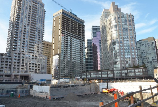 a large number of new high rise buildings just beyond a large hole in the ground where another condo is being built