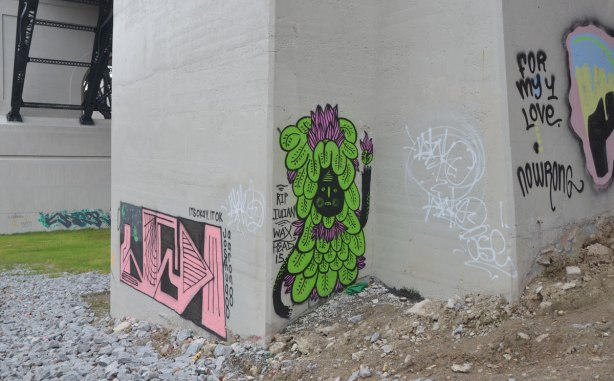 graffiti on concrete bridge supports - creature with black face and covered in green leaves, with a few purple petals on top of the head. words, RIP Julian Waxhead, as well as a pink and black geometric street art painting