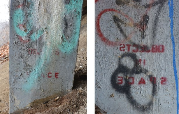 Two sides of the same pole. One side has a stencil in red that says Objects in Space. The other side has the same stencil, but in reverse.