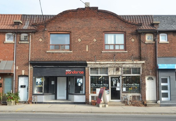 store front, one is an Occult Store, in an old brick building with a curved roofline over the middle of it.