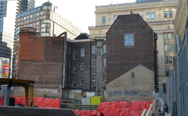 back of a large four storey brick building behind an open hole construction site, taller buildings in the background (College Park)