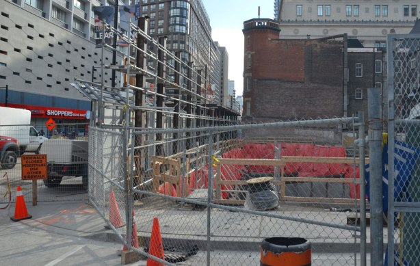 open hole at construction site surround by fence, brick building in the background.