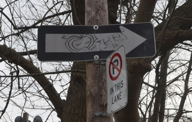 Two faces drawn on a one way sign