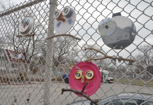 four owls made of recycled goods, foil pie plates, CDs, bottle tops, there feet are wrapped around twigs and they are attached to a chainlink fence