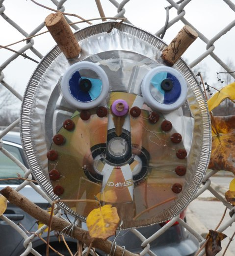 owls made of recycled goods, foil pie plates, CDs, bottle tops, there feet are wrapped around twigs and they are attached to a chainlink fence - two corks for horns